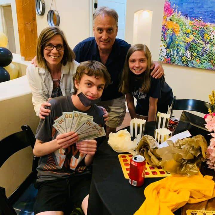 Family of 4 holding cash winnings from Park Senior Villas' Bing Extravaganza Event